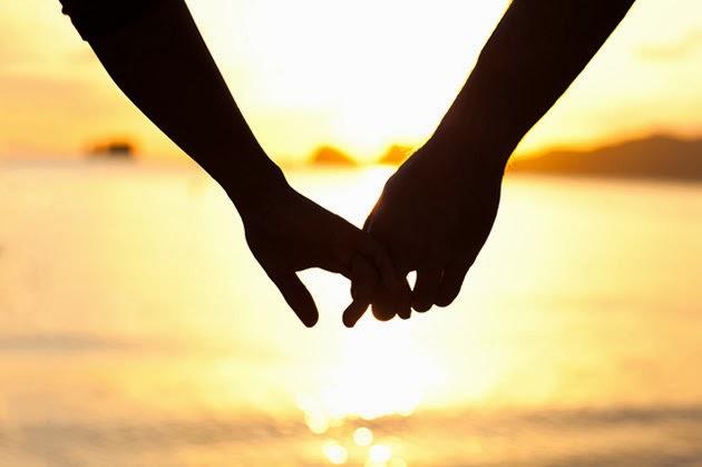 As mãos de um casal frente ao lindo por do sol em uma praia deserta