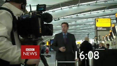Gardner stand using a zimmer in what looks like an airport screengrabed from the countdown to the hour on the BBC News channel