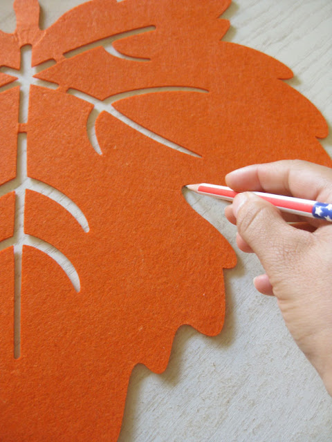 tracing shape of felt leaf placemat onto wood