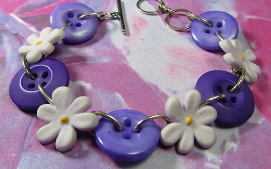 Cute purple daisy bracelet has light purple flowers and dark purple buttons connected with silver loops