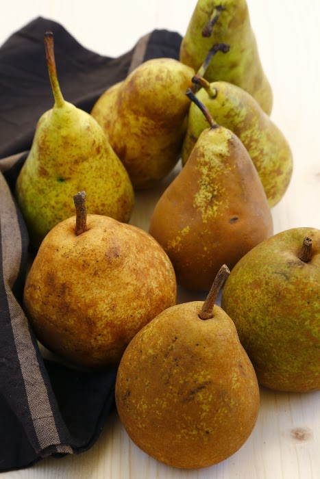 Pears on a wooden board and brown linen