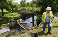 In this July 29, 2012 file photo, a worker monitors the water in Talmadge Creek in Marshall Township, Mich., near the Kalamazoo River as oil from a ruptured pipeline, owned by Enbridge Inc, is vacuumed out the water. (Credit: AP Photo/Paul Sancya, File) Click to Enlarge.