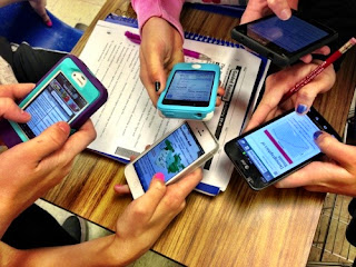 Students using smartphones in the class to finish classwork
