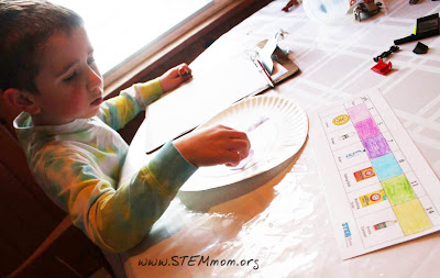 Boy using pH paper to test snow samples in a STEM lab: STEMmom.org