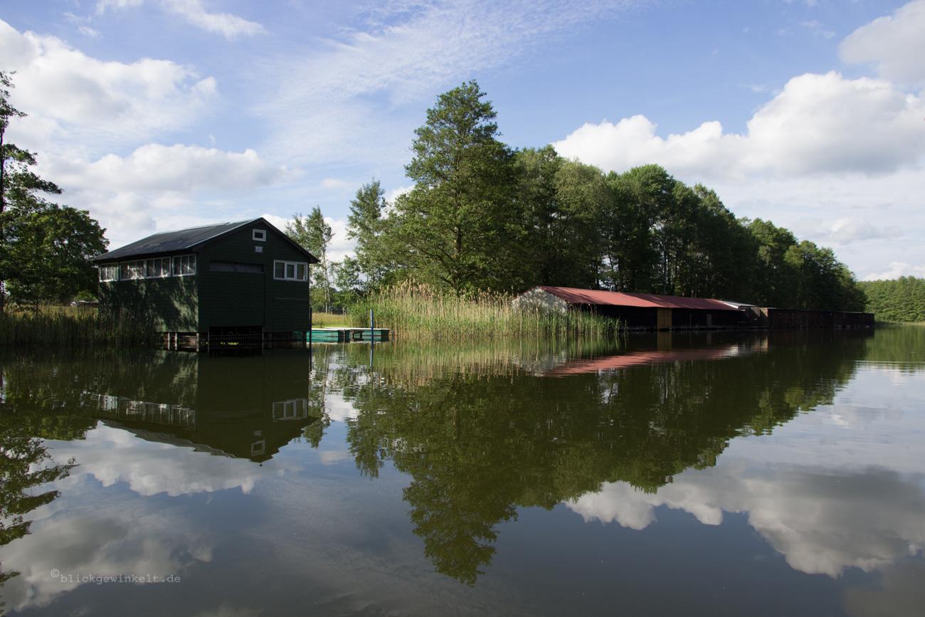 Fluss mit Bootscshuppen und Spiegelung