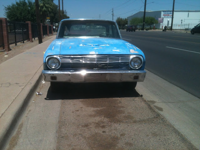Front view of blue 1963 Ford Falcon sedan parked on urban street