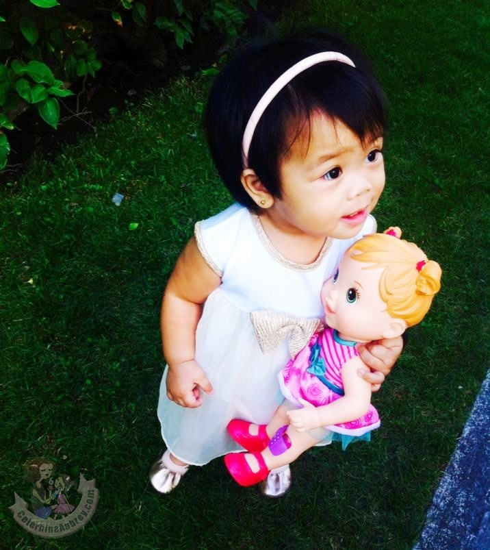 Baby girl on a white dress with her Baby Alive Doll