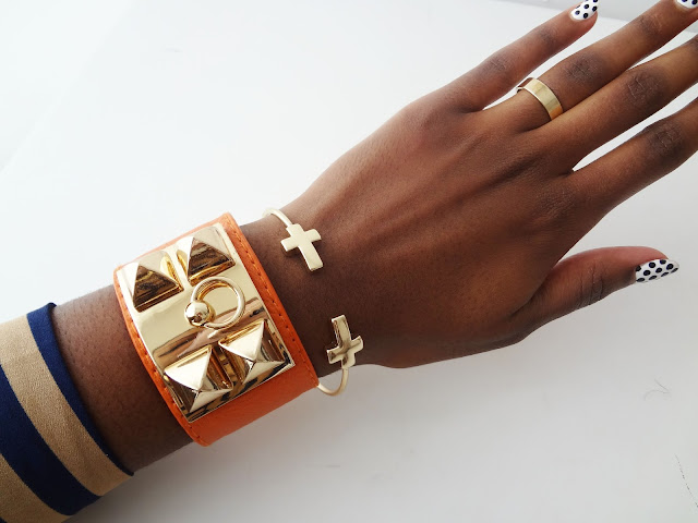 Gold Pyramid Stud Faux Leather Cuff Bracelets orange on wrist.
