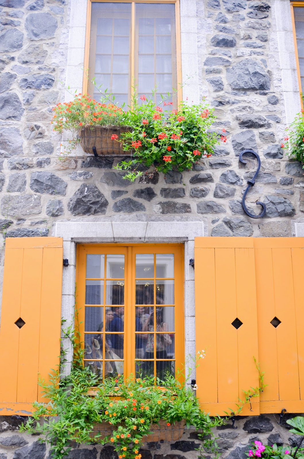 yellow windows and doors with flower baskets in Old Quebec, quebec city, canada summer travel