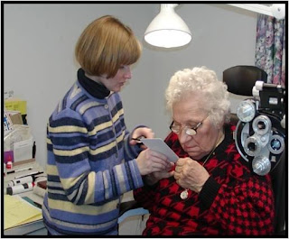 Dr. Casey-Gee gives a woman a low vision examination.