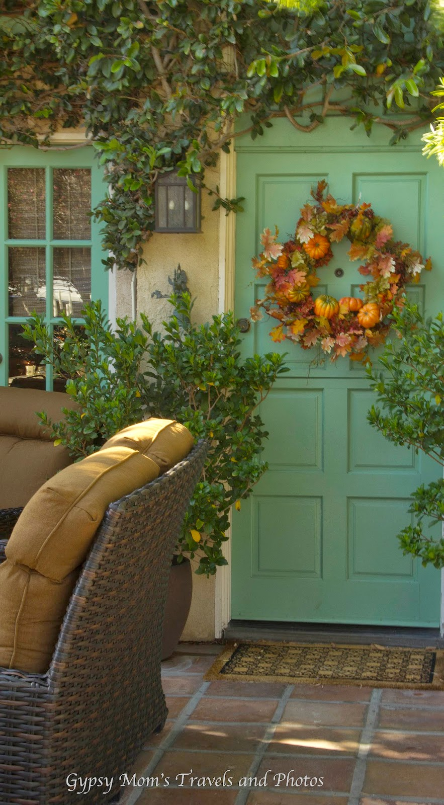 A homey front porch in Corona del Mar with a green door and fall wreath and couches