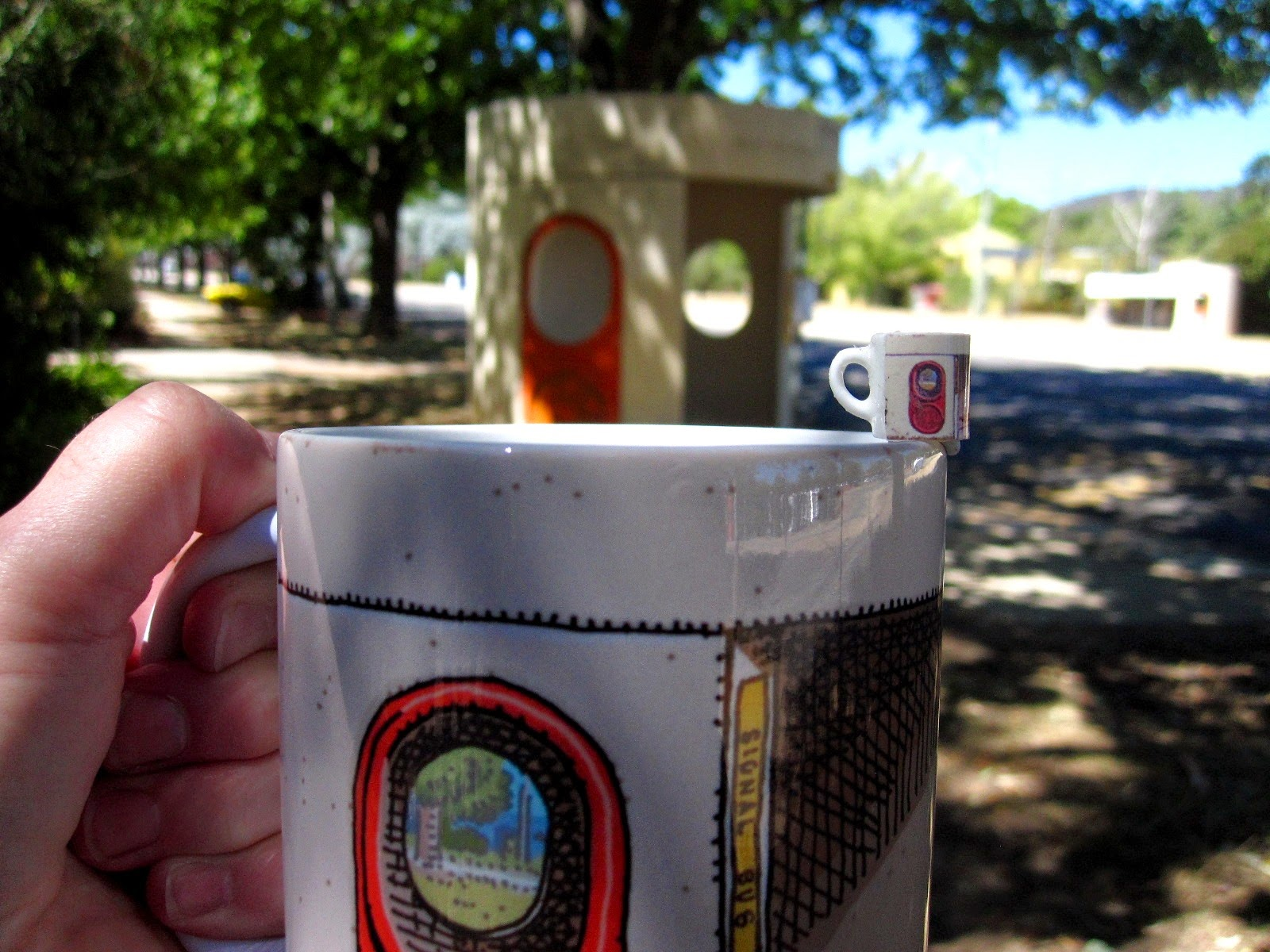 Dolls' house miniature mug with a Canberra bus shelter print, balanced on the edge of a full-sized Canberra bus shelter mug, held in front of a Canberra bus shelter.