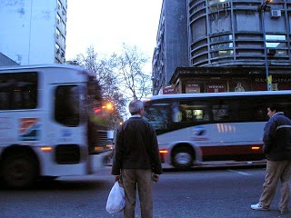 A man on a busy street waiting for vehicles to pass.