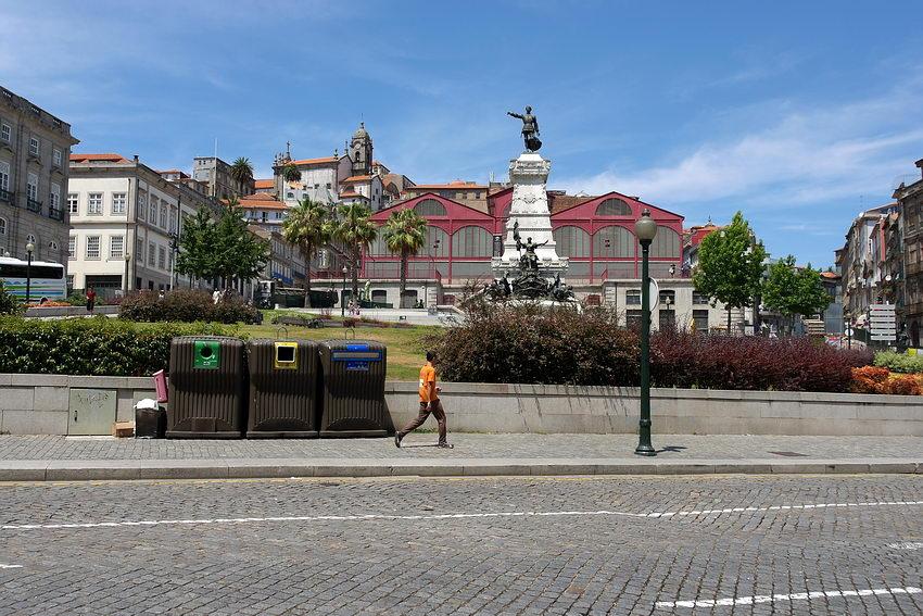 Vista sobre a praça com a estátua centrada na imagem e um rapaz a andar vo passeio