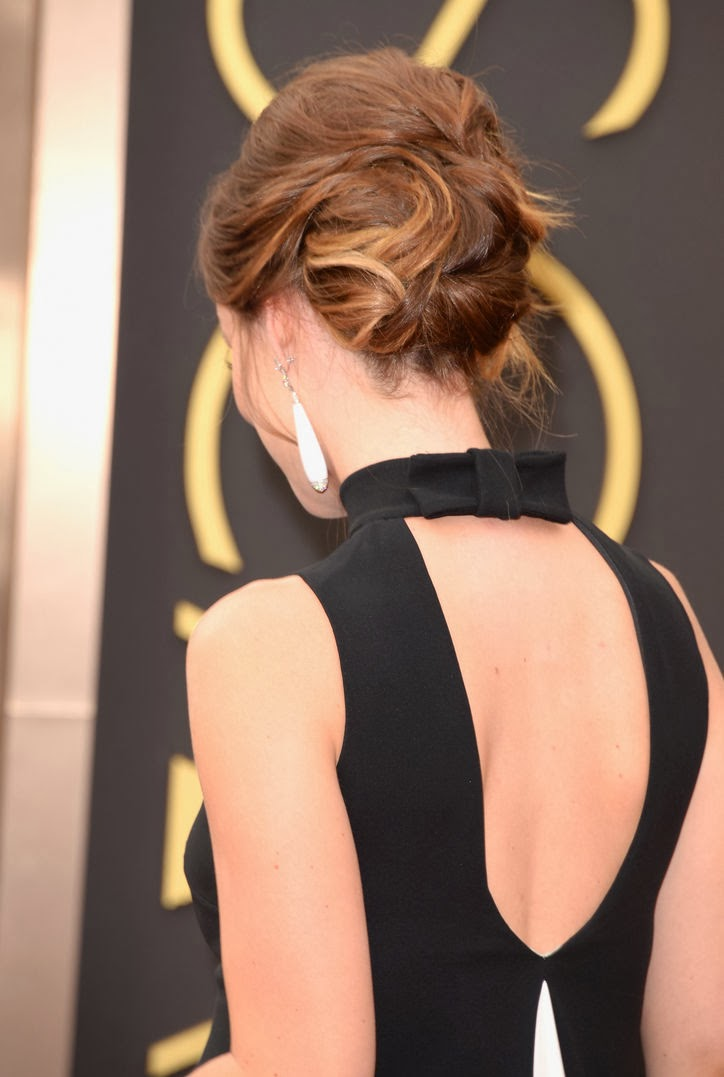 Olivia Wilde has her hair swept back into an elegant bun with some face framing wisps