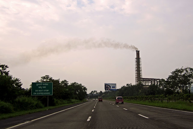 factory spewing smoke in the country-side