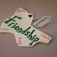 Cut out shape with words - Friendship, deep listening, growth, grace and fun. Heart-shaped symbol in purple and a seperate cut out shape has the word - accountability