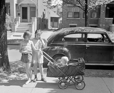 Detroit, Michigan. Little girls wheeling baby brother in a carriage. 1942 July.