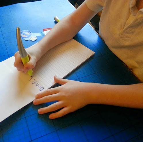 6 year old right handed boy writing with shaped pen