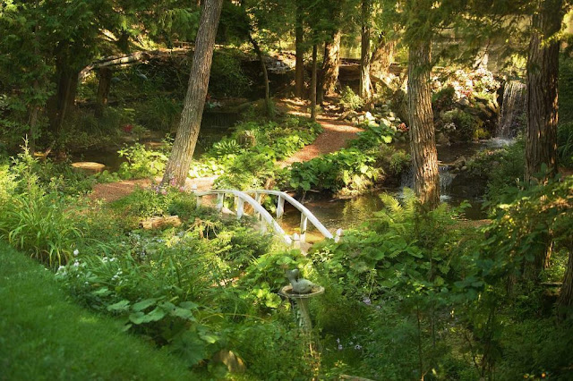 A shaded sanctuary with small waterfalls, stone-paved paths, wildflowers and white wooden footbridge across the running stream, Marigold Springs Orillia