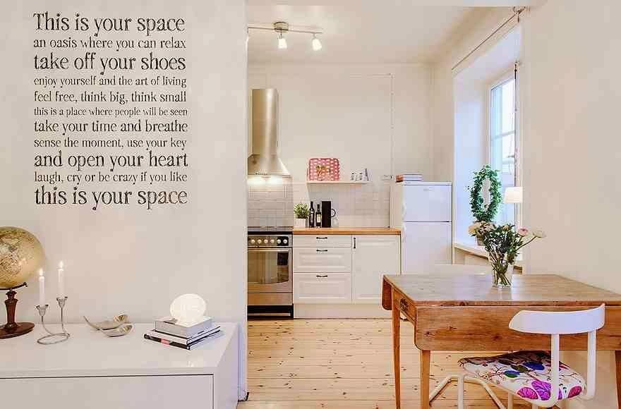 Otwarta kuchnia i typografia na ścianie, drewniany stół, białe wnętrze, białe meble kuchenne, drewniana podłoga w białym wnętrzu