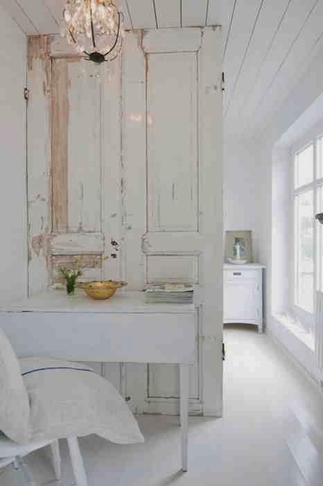 Stare, białe drzwi w białym wnętrzu, podział pokoju za pomocą starych drzwi.