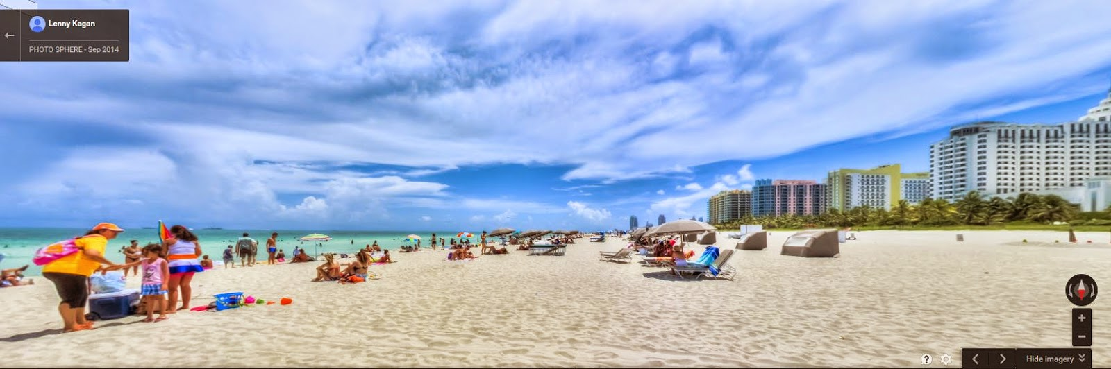 A white, sandy beach with a bunch of vacationers lounging and wearing bright colors.