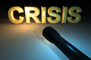 Picture of a flashlight shining on the word crisis.