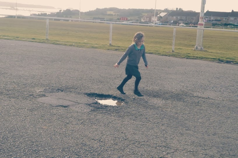 Girl jumping mid air over puddle Gelliswick Hakin Pembrokeshire