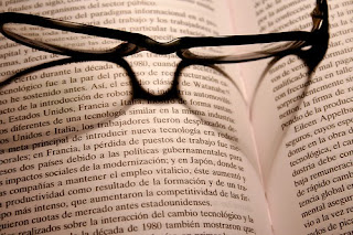 "Photo of reading glasses over an open book. The subtitle reads ""Lee un Buen Libro"" in Spanish."