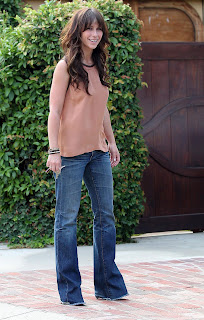 Jennifer Love Hewitt smiles for photographers in front of her home