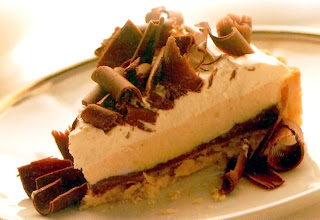 Classic recipe for the three layered chocolate pie (Mississippi mud pie) served as a wedge and topped with chocolate curls.