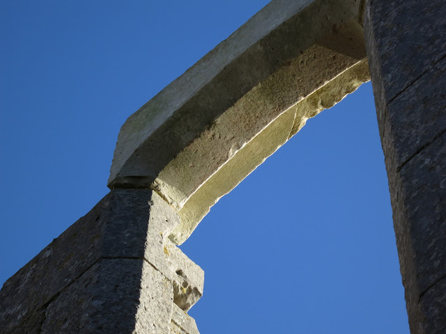 Empty stone arch against blue sky