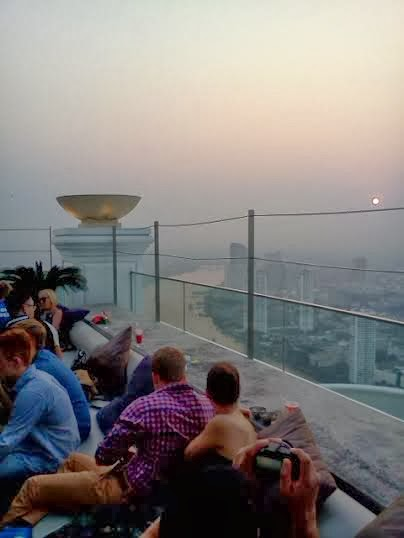 Hipster tourists viewing the smoggy sunset from the Sky Bar in Bangkok.