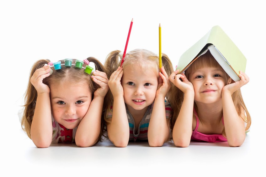 Pic of 3 girls with paint, pencils and a book on their heads respectively