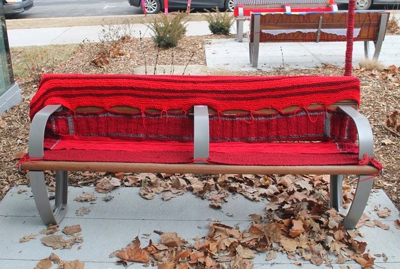 Bench covered with red knitted or crocheted horizontal panels across the seat and draped back-to-front over the backrest of the bench.
