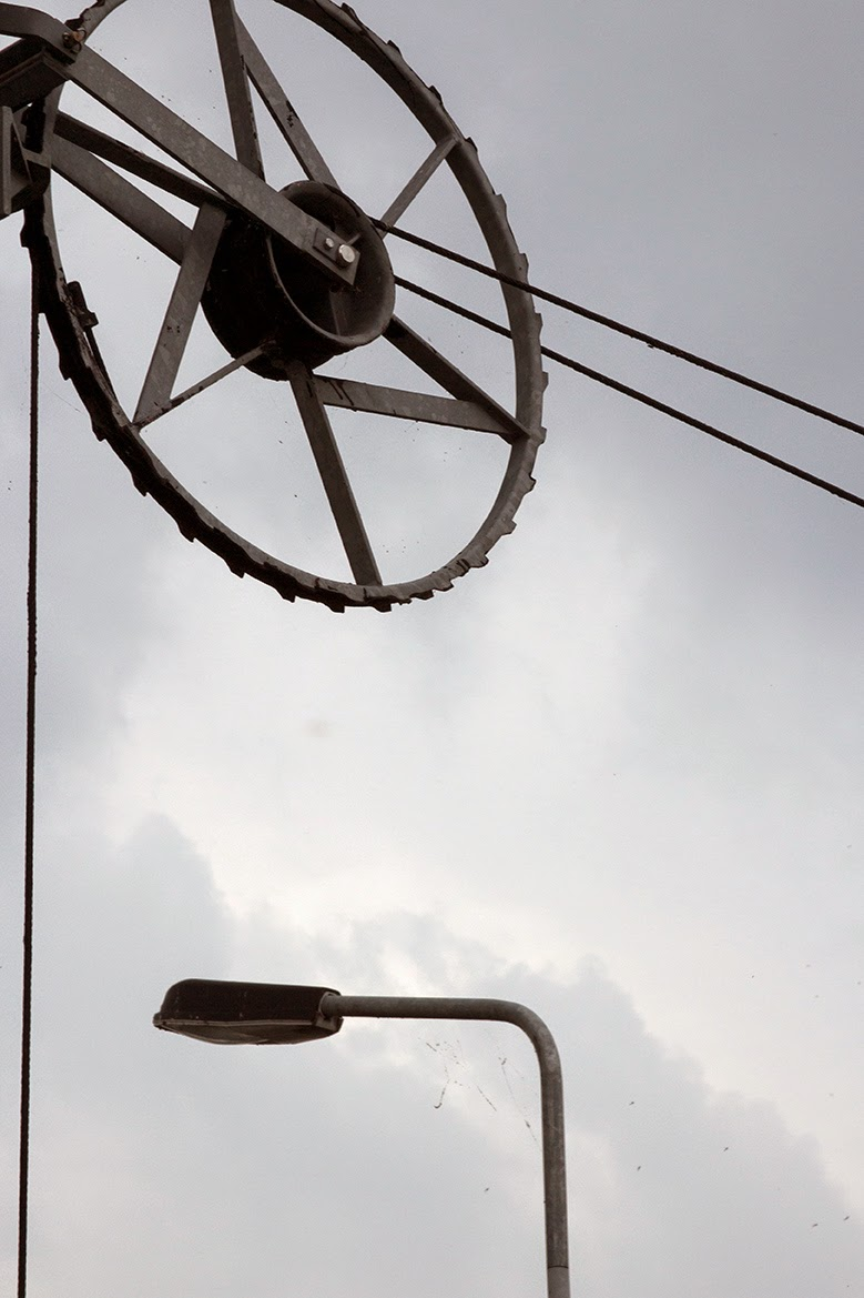wheel and lamppost against grey sky