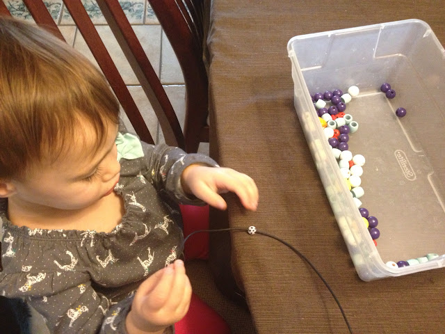 toddler playing with wooden beads