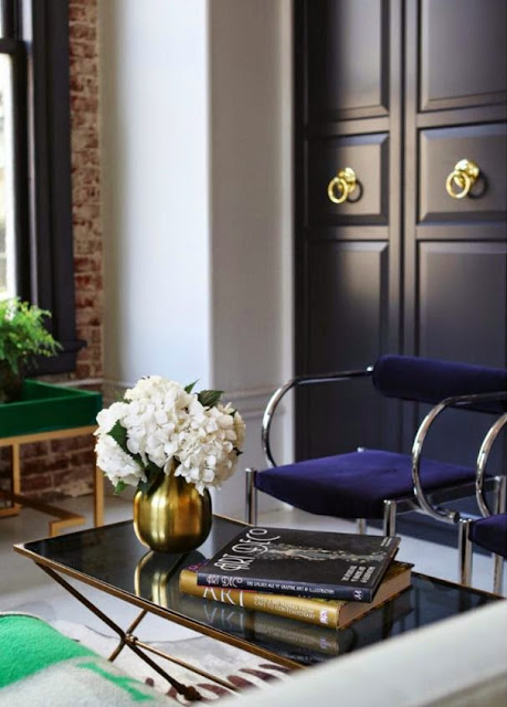 vignette black and gold table black painted doors pop of green color
