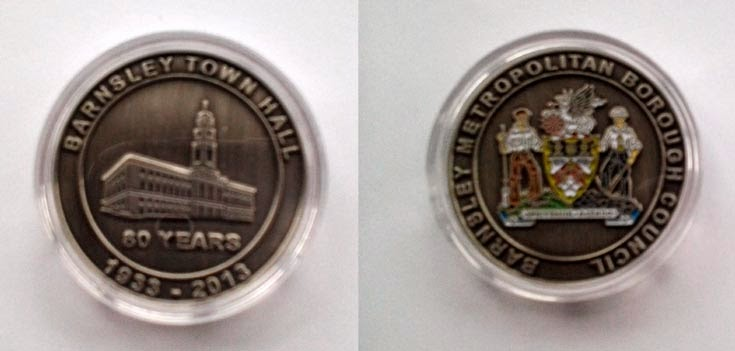 Two sides of a commemorative medallion.  An image Barnsley Town Hall with the words 80 years underneath.  Surrounding the image are the words Barnsley Town Hall 1933-2013.  The other side shows the Barnsley Coat of Arms.