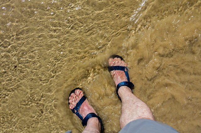 standing in shallow water with sandals on