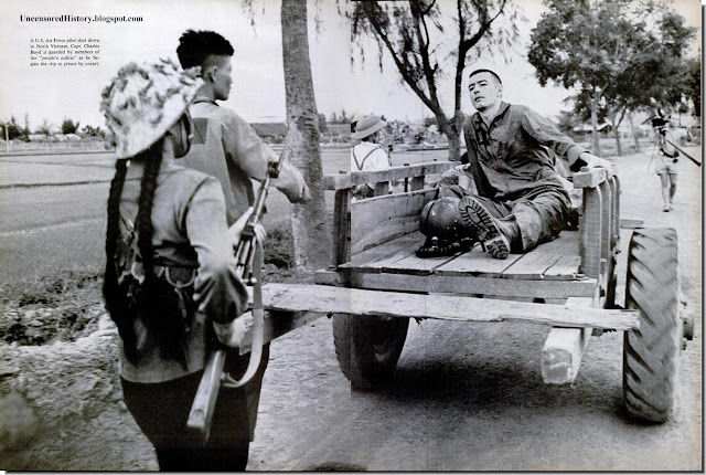 North Vietnam militia escorts American prisoner bullock cart