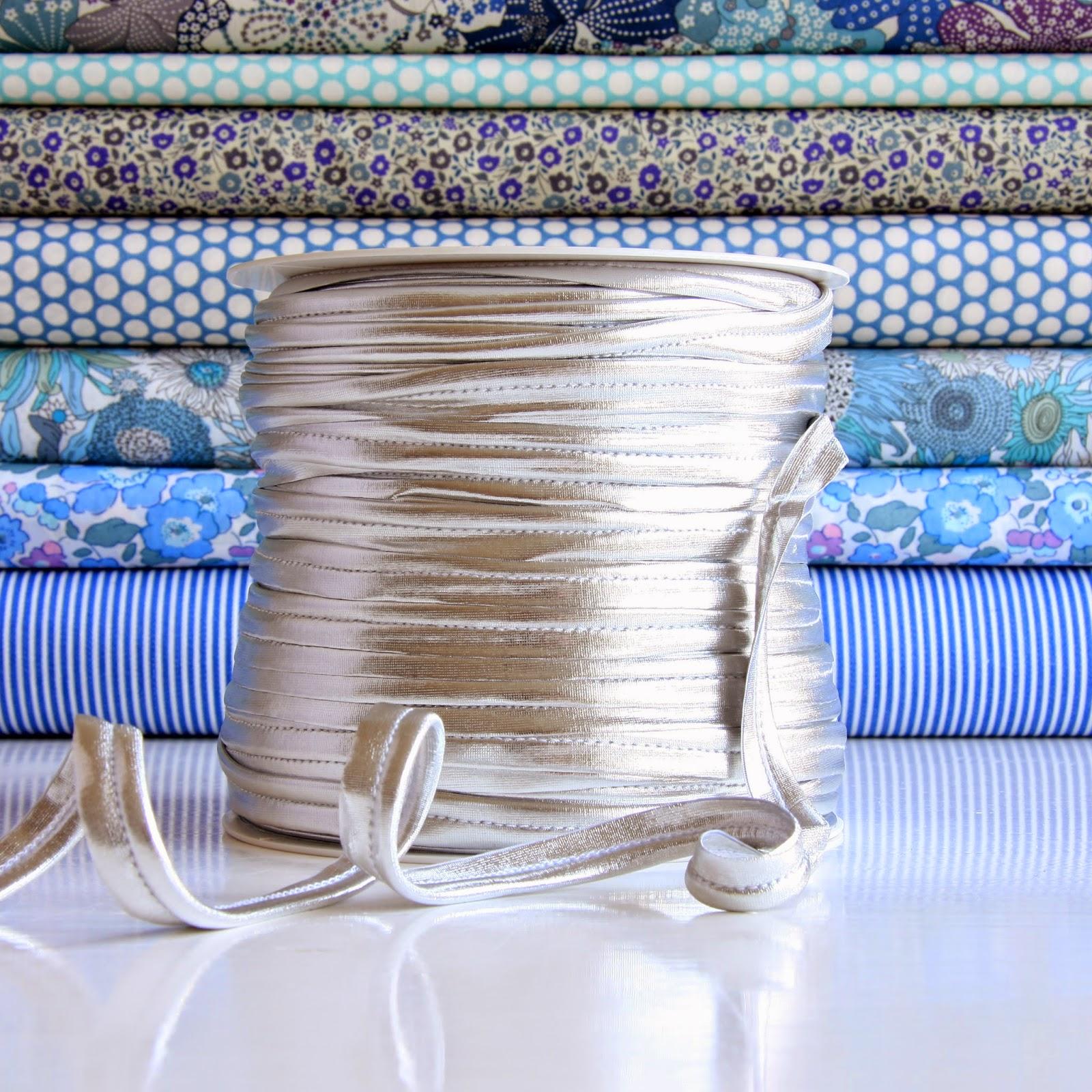 Tittebånd elastisk og sølvfarvet.