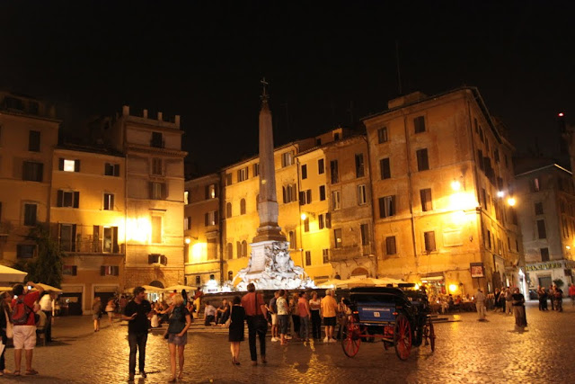 The Fontana del Pantheon is crowded with the tourists at night in Rome, Italy