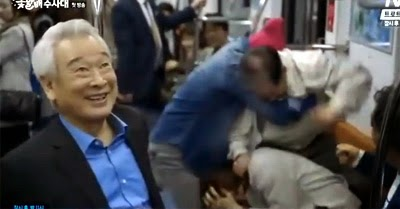 Joon Hyuk laughs as the boys get into a scuffle on the subway.