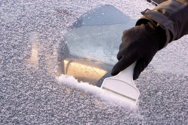 Scraping frost off of a windshield with a small ice scraper.