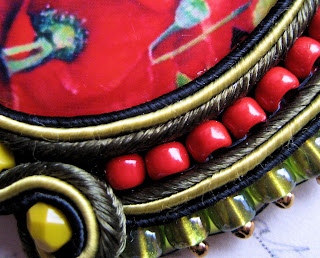 A closeup of soutache curves punctuated by rows of seed beads.