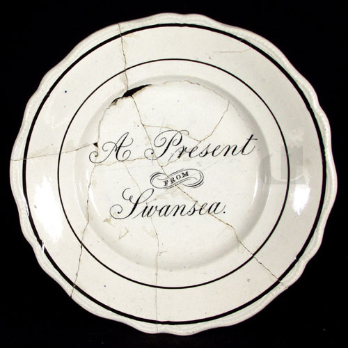 chipped and cracked plate reading 'A Present from Swansea' in crisp black copperplate script