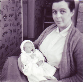 A young mum cradling a small baby, there is a vegetable design on the wallpaper behind, very 1960s.