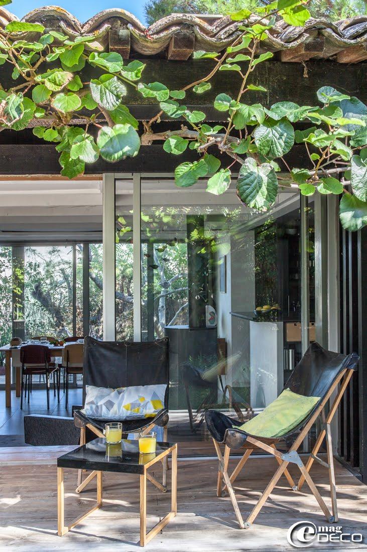 Sur la terrasse de Chloé Sanier, designer textile et créatrice de la marque Marcelise, chaises pliantes en bois naturel et cuir noir, petite table basse Habitat